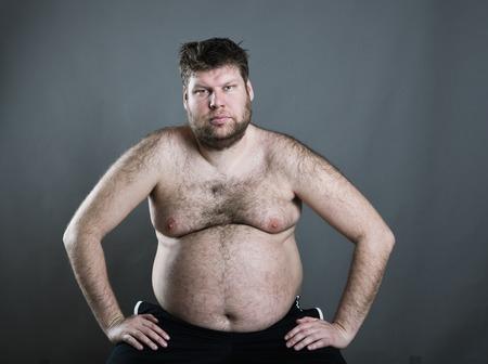naked man: Sentado hombre gordo aislado en fondo gris