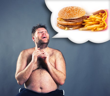 Fat funny man dreaming about  hamburger isolated on gray