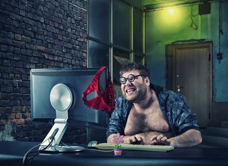 Fat smiling man sitting at desk looking at computer screen and writing to dating web Stock Photo