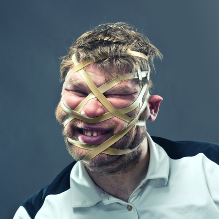 elastic: Freak man with rubber on his face isolated on gray Stock Photo