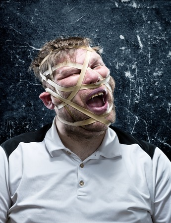 freak: Freak man with rubber on his face isolated over gray background