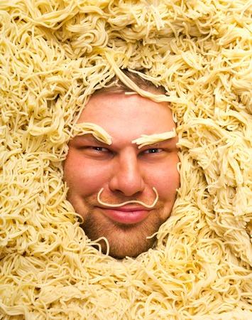 boor: Happy mans face in pasta, closeup Stock Photo