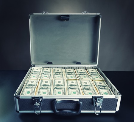 Open case full of dollar cash on gray