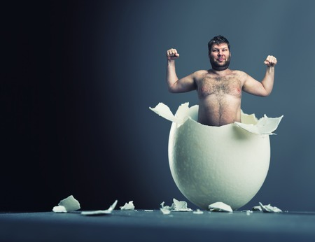 Close-up picture of broken egg with man isolated on gray background photo