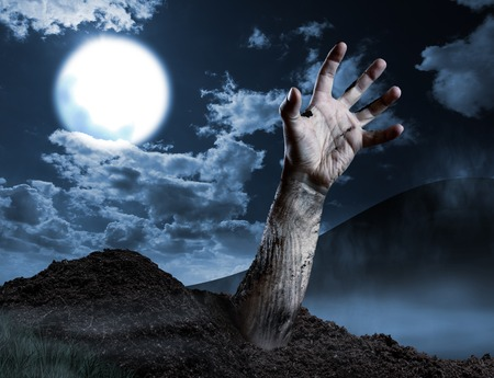 rising dead: Zombie hand coming out of his grave. Full moon, halloween night