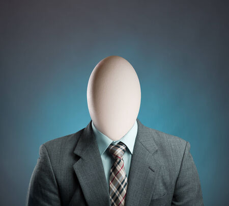 Businessman with egg head on blue photo