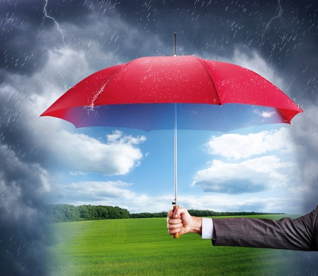 weather protection: Businessman hand with an red umbrella with sunny nature view