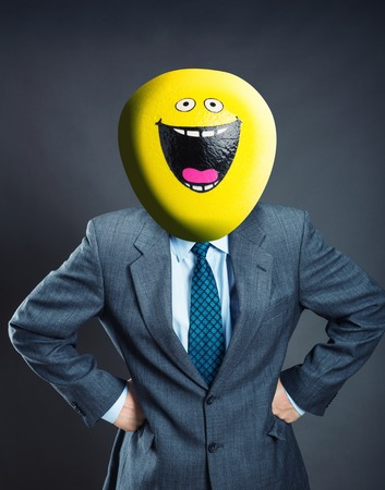 humor mask: Businessman with smiley face instead of his head isolated on gray background