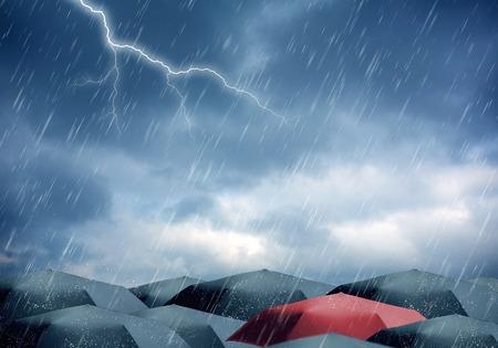 Zwarte en rode paraplu onder regen en onweer