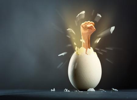 Close-up foto van gebroken ei met de hand op een grijze achtergrond Stockfoto
