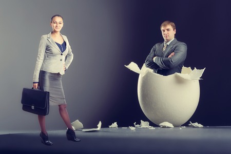 Picture of broken egg with man and woman isolated on gray background photo