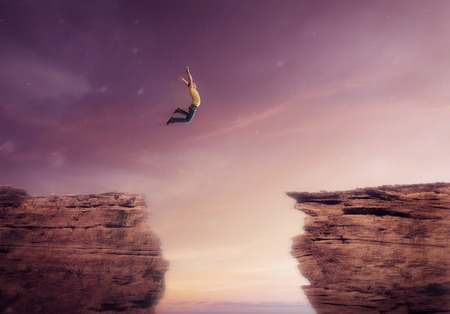 若い男が、崖の間から飛び降りる 写真素材