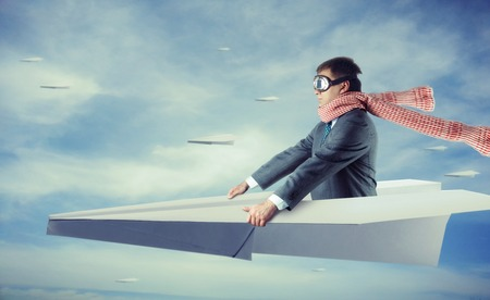 Businessman flying on big paper plane and wearing goggles and scarf isolated on sky background