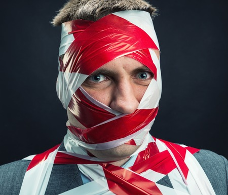 taped: Victum man with stripped duct tape over body Stock Photo