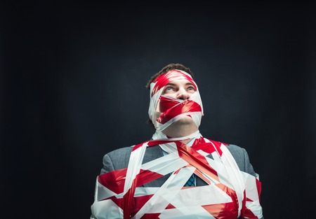 gagged: Victum man with stripped  red and white duct tape over body Stock Photo