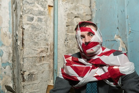 Victum man with stripped  red and white duct tape over body in old house photo