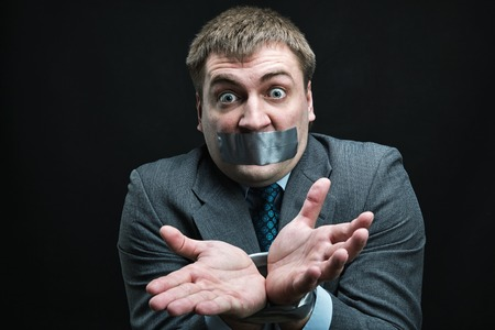 Businessman with mouth and hands  covered by masking tape preventing speech, studio shoot photo