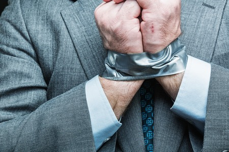 oppress: Businessman with hands covered by masking tape, studio shoot Stock Photo
