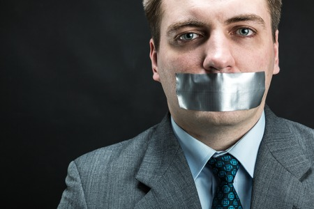 outspoken: Man with mouth covered by masking tape preventing speech, studio shoot