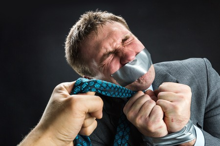 gagged: Man in capture with mouth and hands covered by masking tape preventing speech, isolated on black