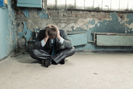 Poor homeless businessman sitting on old cellar photo