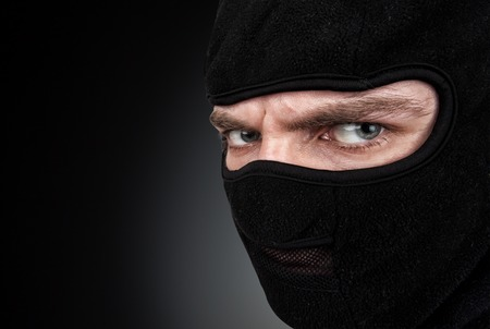 thievery: Portrait of man in a mask on black background