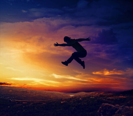 cliff jumping: Black silhouette of man jumping off a cliff