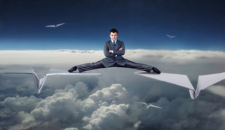 stunts: Businessman flying on big paper planes in split Stock Photo