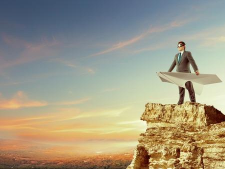 Zakenman verblijf op de top van de berg met grote witte papieren vliegtuigje en het dragen van beschermende brillen die op hemelachtergrond Stockfoto
