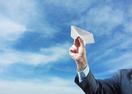 Businessman holding white  paper plane in his hand