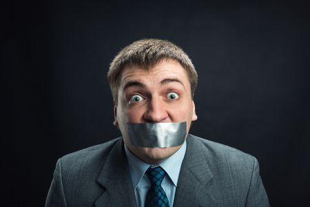 taped: Young man with mouth covered by masking tape preventing speech, studio shoot