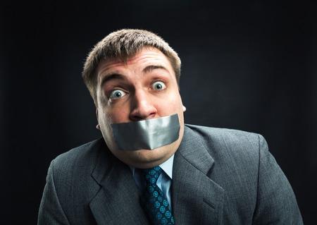 Uomo sorpreso con la bocca coperta da nastro adesivo che impedisce il discorso, riprese in studio