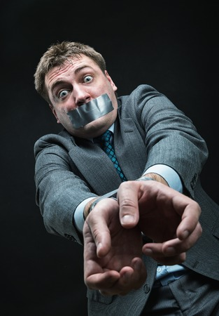 outspoken: Man with mouth and hands  covered by masking tape, studio shoot