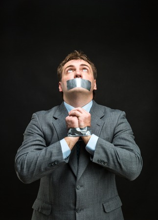 inhibit: Man with mouth and hands covered by masking tape preventing speech, isolated on black Stock Photo