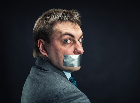 Man with mouth covered by masking tape ,studio shoot photo
