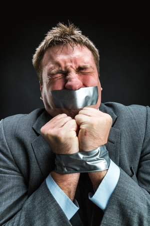 oppress: Man with mouth and hands  covered by masking tape preventing speech, studio shoot Stock Photo