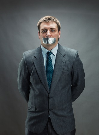 gagged: Man with mouth and hands covered by masking tape preventing speech, isolated on gray