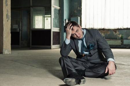 Poor homeless businessman sitting in old house photo