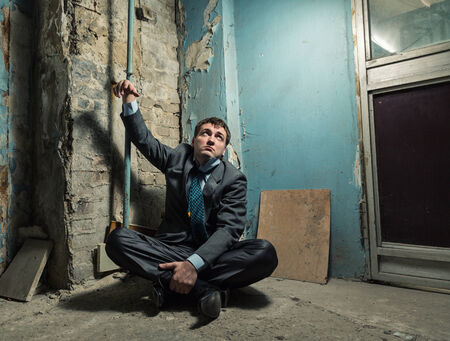handcuffed: Arrested man with handcuffed hand in old cellar of house Stock Photo