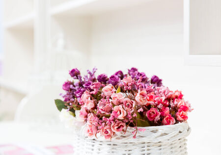 Beautiful bouquet of bright flowers in basket on white table photo