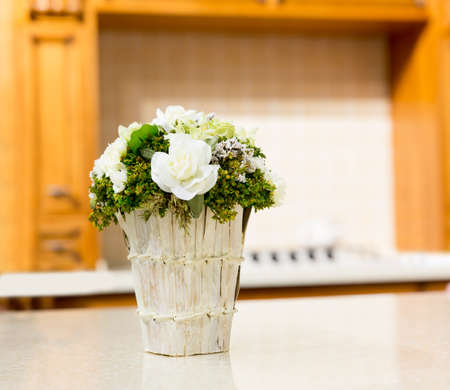 Beautiful bouquet of white rose flowers in basket on white table photo