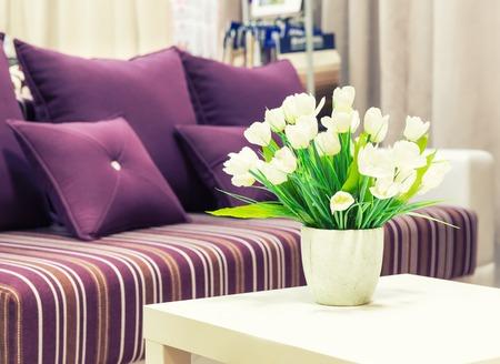 vase: Flowers in a vase against sofa with velvet pillows