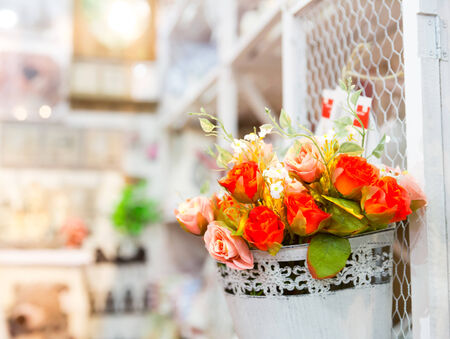 Beautiful bouquet of bright rose flowers in basket on white table photo