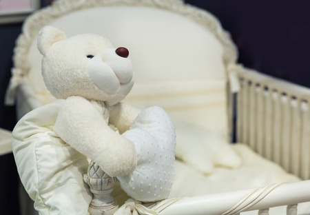 Baby bedroom with white teddy bear on the bed photo
