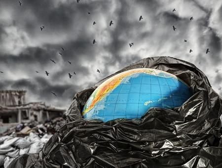 Earth globe in trash against dramatic sky photo