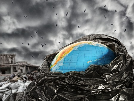 Earth globe in trash against dramatic sky Stock Photo