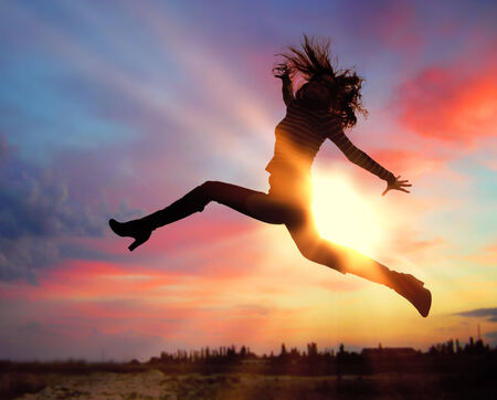 Silhouette of excited woman jumping at sunset Stock Photo - 29986635