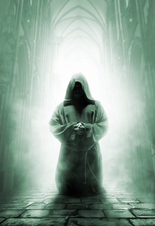 Mystery medieval monk praying on kneels in dark temple corridor Stock Photo - 29986758
