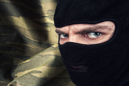 Serious man in a balaclava mask against military camouflage background Zdjęcie Seryjne