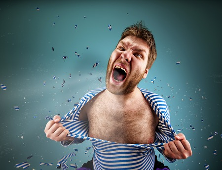 Furious man is tearing clothing on himself and are screaming Stock Photo
